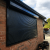 A Black Domestic Security Shutter In A Residential Garden