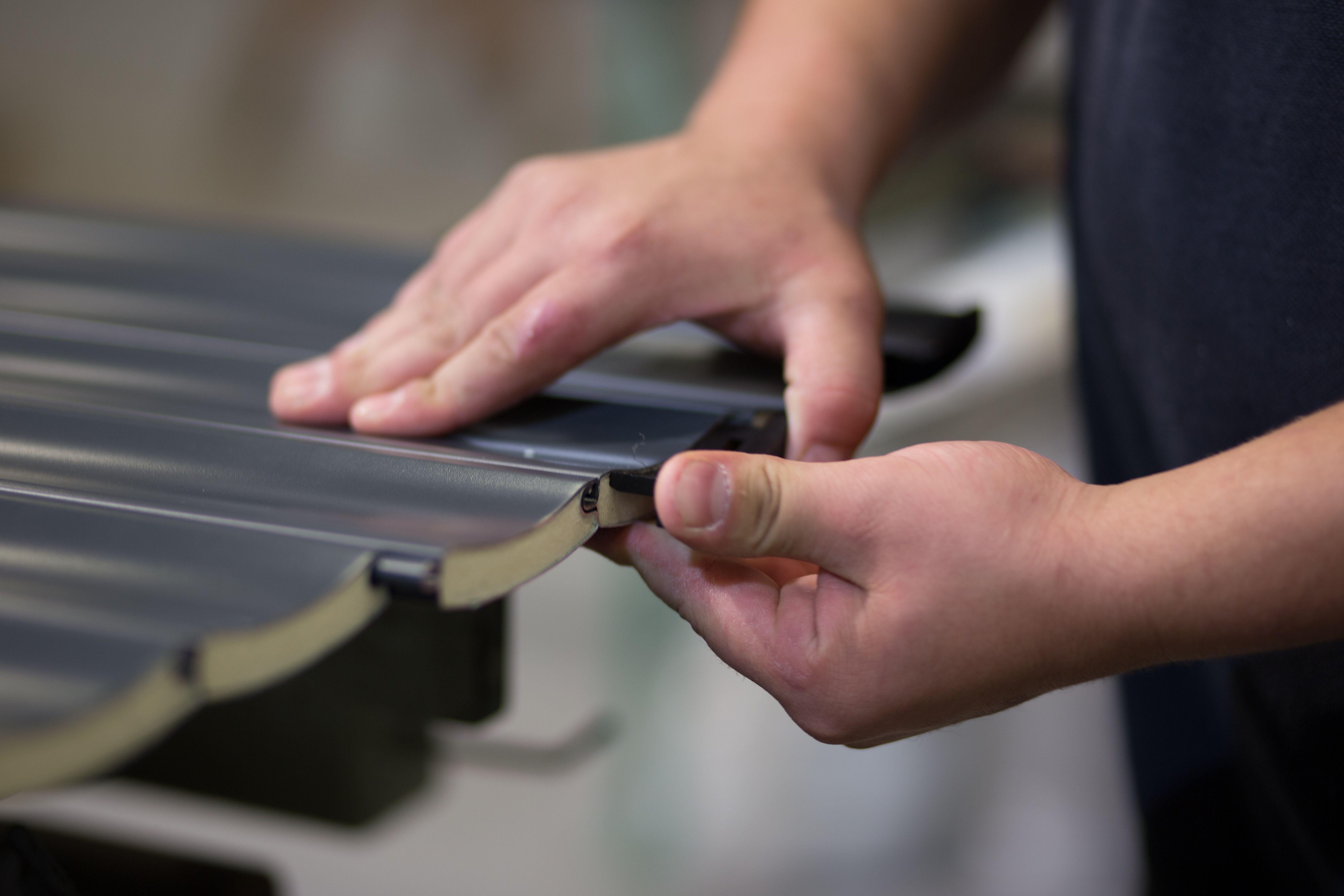 Factory Worker Assembling Roller Garage Door Parts