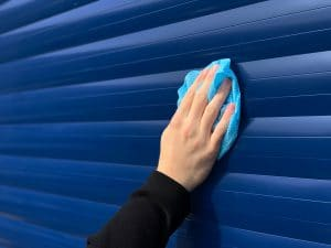 A Roche Engineer Cleaning An Aluminium Roller Shutter