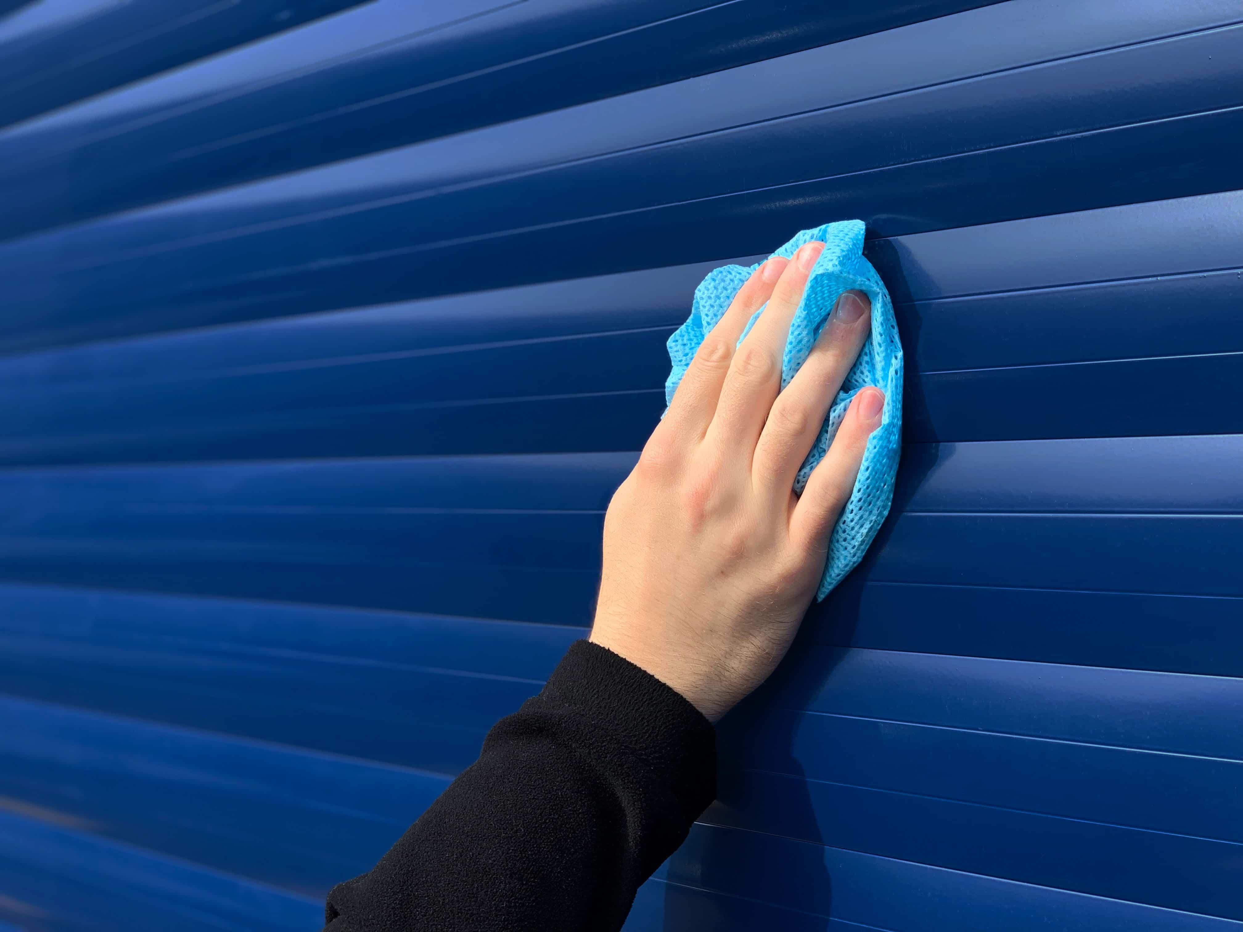 A Roche Engineer Cleaning An Aluminium Roller Shutter